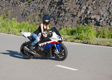 Blonde girl rides on modern motorcycle. Stock Images