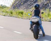 Blonde girl rides on modern motorcycle. Royalty Free Stock Photos