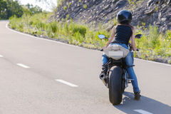 Blonde girl rides on modern motorcycle. Stock Photos