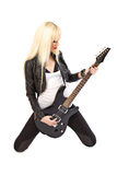 Blonde girl rockstar in playing black guitar. Sexy blonde girl rockstar in black leather jacket playing black electric guitar Stock Photography