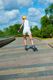 Blonde girl on roller skates rides Royalty Free Stock Image
