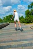 Blonde girl on roller skates rides Royalty Free Stock Image