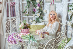 Blonde girl in the room with flowers. Beautiful blonde sitting in the flower room Stock Image
