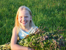 Blonde girl's portrait. Little blonde girl with fresh peppermint on green field background stock photo