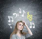 Blonde girl scratching head, music notes. Close up of a blonde businesswoman scratching her head and thinking. She is wearing a gray sweater and trying to recall Royalty Free Stock Photo