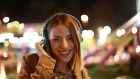 Blonde girl shaking her head to the rhythm of music with headphones stock video