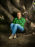 Blonde girl in shirt and jeans sitting under big tree Stock Images