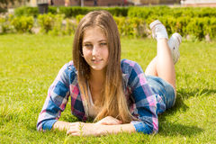 Blonde girl in shirt lying on grass at sunny day Royalty Free Stock Images