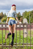 Blonde girl in short denim shorts with roses wreath on head Royalty Free Stock Image