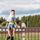 Blonde girl in short denim shorts with roses wreath on head Royalty Free Stock Photo