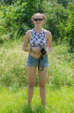 Blonde girl in shorts with a camera in hands Stock Image