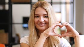 Blonde Girl Showing Heart , made by hands royalty free stock image