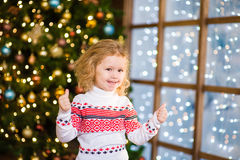 Blonde girl showing thumbs up on the background of Christmas tre. E Royalty Free Stock Image