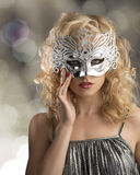 Blonde girl with silver mask on the face. Pretty blonde girl with curly hair takes one silver mask, she is in front of the camera and takes the mask on the face stock photo