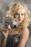 Blonde girl with silver mask in front royalty free stock photos