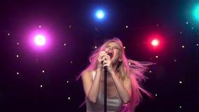 Blonde girl singing and dancing with retro microphone. Karaoke. Slow motion. Beautiful blonde girl with flying long hair singing and dancing with retro stock video