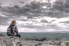 Blonde girl sits alone at edge  above the abyss royalty free stock images