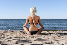 Blonde girl sits on the beach and meditate. Blonde girl in a black bathing suit sits with his back to the beach in the sand and meditate royalty free stock image
