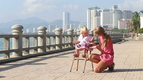 Blonde Girl in Sits on Chair and Mother Claps stock footage