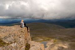 The blonde girl sits dangerously alone on the edge of the cliff royalty free stock photography