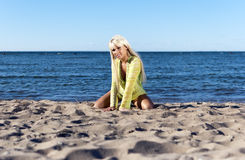 Blonde girl sits near the sea on his knees Stock Image