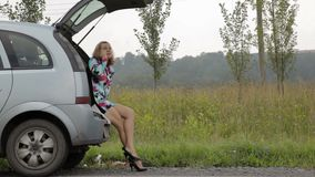 Blonde girl sits in open trunk of her broken car with blinking emergency signal on a country road stock video footage