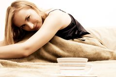 Blonde girl sitting on the bed. Blonde beautiful girl sitting on the bed in the morning royalty free stock image