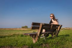 Blonde girl sitting on a bench. In a meadow green grass royalty free stock photos