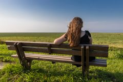 Blonde girl sitting on a bench. In a meadow green grass royalty free stock photo
