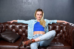 Blonde girl is sitting on a brown sofa in the background of a gr Stock Image