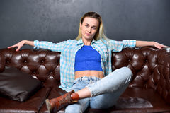 Blonde girl is sitting on a brown sofa in the background of a gr Royalty Free Stock Photography