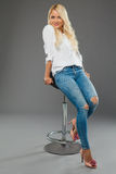 Blonde girl sitting on the chair wearing jeans and white shirt Royalty Free Stock Images