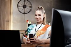 Blonde girl sitting at desk using mobilephone Stock Photos