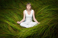 Blonde girl sitting on green grass and meditating. Stock Photo