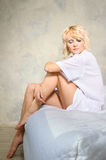 Blonde girl sitting lonely on bed Stock Images