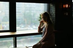 Blonde girl sitting near window at cafe. royalty free stock image