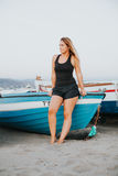 Blonde girl sitting on an old blue boat at the beach. royalty free stock photography