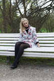 Blonde girl sitting on a park bench Royalty Free Stock Photography