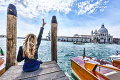 Blonde girl sitting on the pier in Venice. Back view Stock Photos