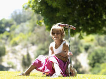 Blonde girl (6-8) sitting on push scooter in park, smiling, portrait Royalty Free Stock Images