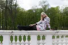 Blonde girl sitting on the railing Royalty Free Stock Photo