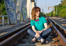 Blonde girl sitting on the railroad Stock Photos