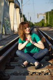 Blonde girl sitting on the railroad Royalty Free Stock Photography