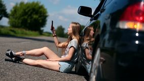 Blonde girl sitting on road near her broken car stock footage