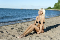 Blonde girl sitting on shore blue sea Royalty Free Stock Photo