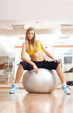 Blonde girl sittinig on silver ball in fitness gym Stock Image