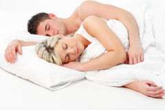Blonde girl sleeping with a boy in bed Stock Image