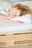 Blonde girl sleeping on white bed Royalty Free Stock Photo