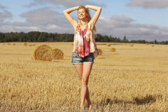 Blonde girl in sloping field Stock Photography