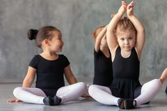 Girl stretch before a ballet. A blonde girl and a small Asian girl in black swimsuits, white tights and pointe shoes sit on the pound and stretch before a ballet stock photos